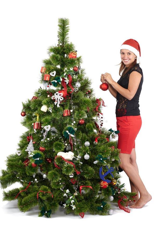 H?rlig le kvinna i jultomtenlock som dekorerar julgranen, p? vit bakgrund arkivfoto