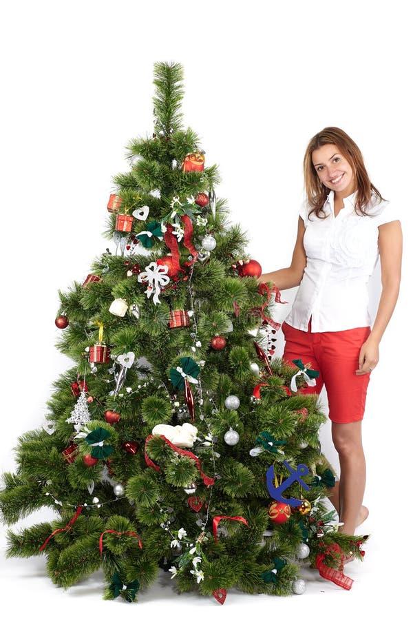 H?rlig le kvinna i r?tt vitt dekorera jultr?d, p? vitt royaltyfri foto