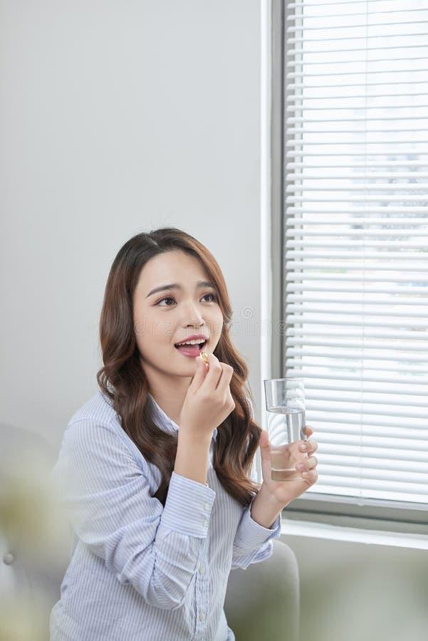 H?rlig le kvinna som tar vitaminpreventivpilleren Dietary supplement royaltyfri foto