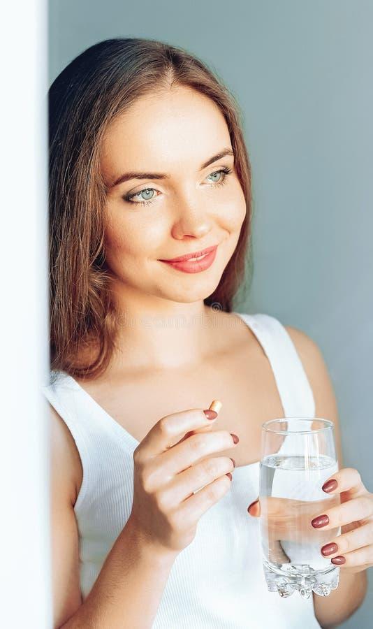 H?rlig le kvinna som tar vitaminpreventivpilleren Dietary supplement arkivfoton