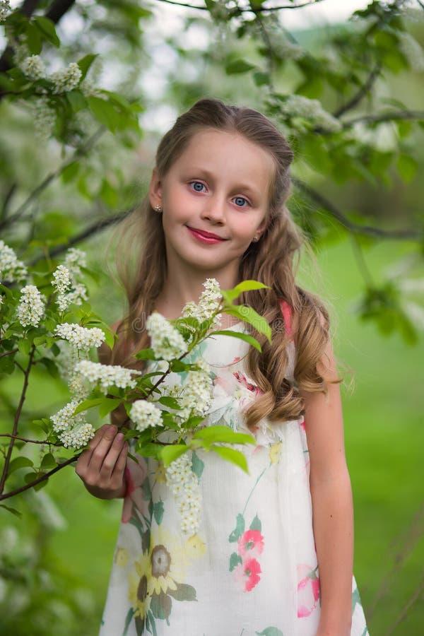 H?rlig liten flicka i den blommiga tr?dg?rden med l?ngt h?r arkivfoton