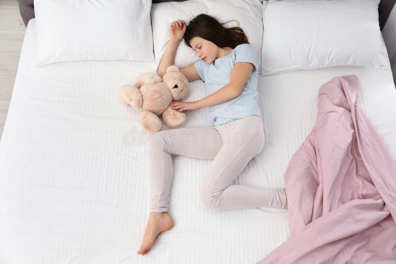 H?rlig liten flicka med nallebj?rnen som sover i s?ng royaltyfria bilder