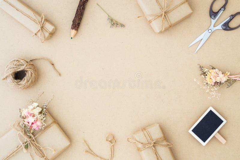 H?rlig liten handgjord packe f?r DIY-g?vaask med blommor och dekorativt rep p? brun bakgrund retro stiltappning plant royaltyfria bilder
