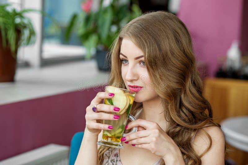 h?rlig lockig h?rkvinna Te med mintkaramellen och citruns Begrepp av livsstilen, drinkar och sunt ?ta arkivfoton