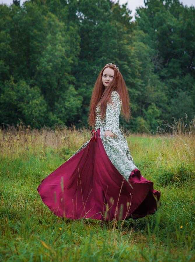 H?rlig lycklig kvinna i l?ng medeltida kl?nningdans royaltyfri foto