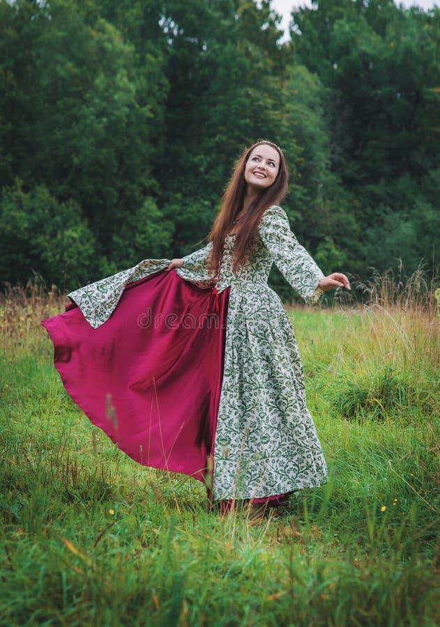 H?rlig lycklig kvinna i l?ng medeltida kl?nningdans royaltyfria bilder