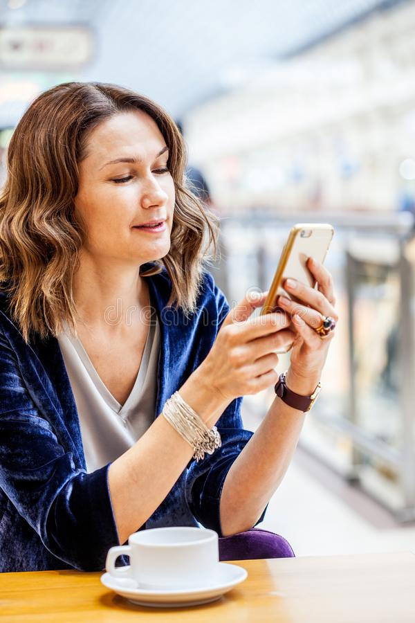 H?rlig medel?lders kvinna med en smartphone i hand royaltyfria bilder