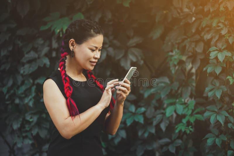 H?rlig mogen asiatisk kvinnlig modell med utomhus- Smartphone royaltyfria foton