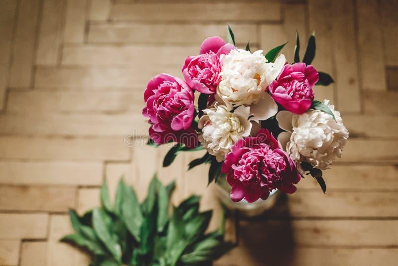 H?rlig rosa och vit pionbukett i exponeringsglaskrus p? det lantliga tr?golvet, framl?nges som ?r lekmanna- Blom- dekor och ordni arkivfoton