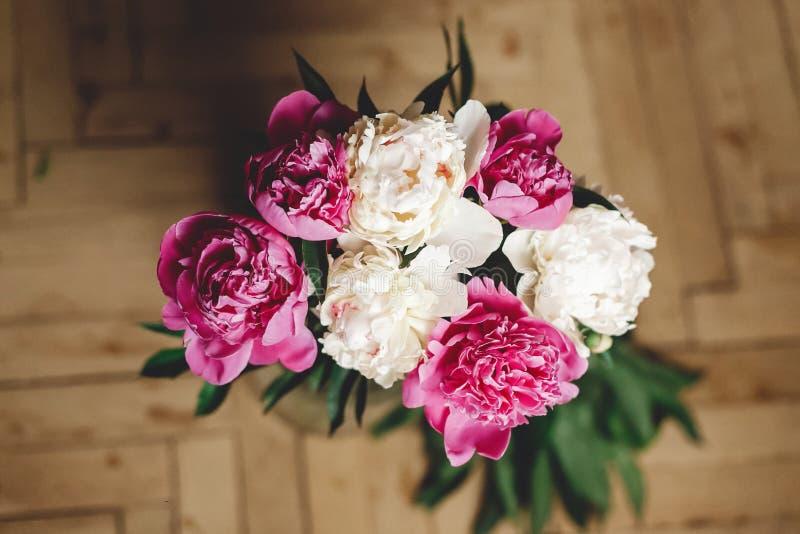 H?rlig rosa och vit pionbukett i exponeringsglaskrus p? det lantliga tr?golvet, framl?nges som ?r lekmanna- Blom- dekor och ordni arkivbild