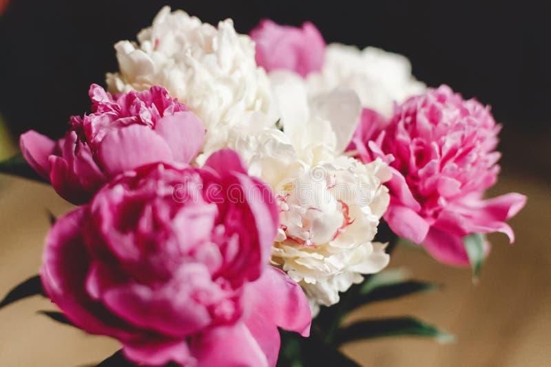 H?rlig rosa och vit pionbukett i exponeringsglaskrus p? det lantliga tr?golvet, framl?nges som ?r lekmanna- Blom- dekor och ordni royaltyfri bild