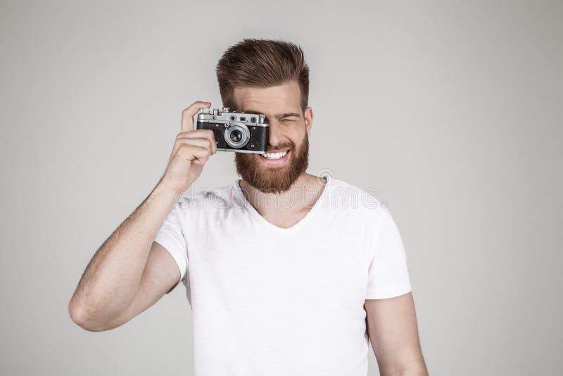 H?rlig sexig sk?ggig man med en h?rlig h?rstil poserar med en gammal kamera och leenden iklätt poserar ett omslag, framme royaltyfri bild