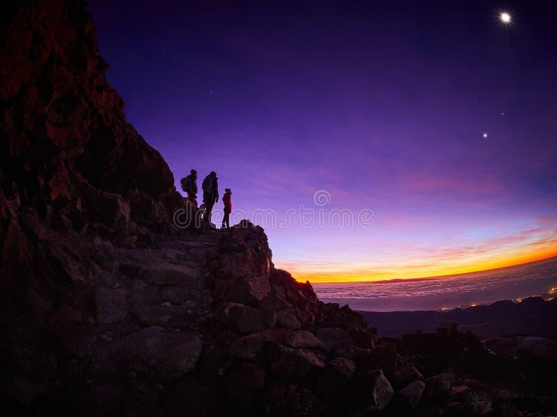 H?rlig sikt uppifr?n av det Teide vulkanmaximumet, Pico del Teide, med turister p? soluppg?ng i Tenerife, Spanien arkivfoton