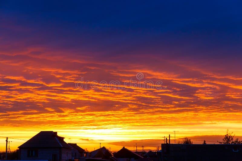 h?rlig solnedg?ng F?rgrik dramatisk himmel p? solnedg?ngen Taken av lantliga hus på bakgrunden av solnedgången royaltyfria foton
