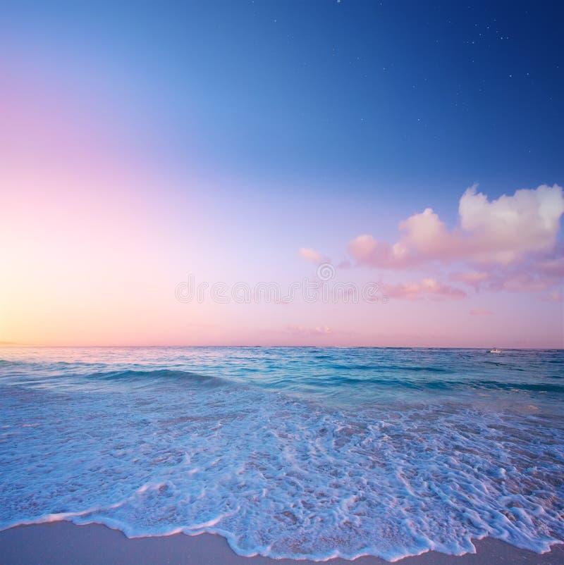 H?rlig soluppg?ng ?ver den tropiska stranden; paradissommarsemester royaltyfri bild