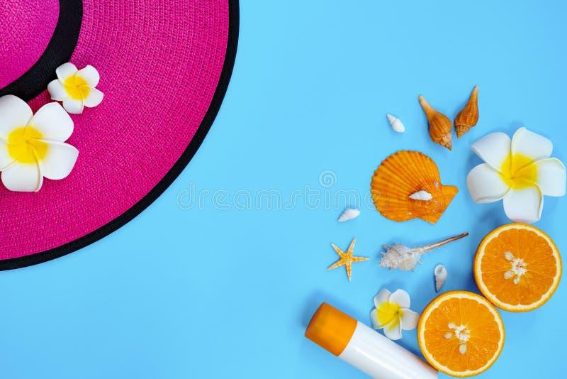 H?rlig sommarferie, strandtillbeh?r, apelsin, hatt och sunblock p? bl?a bakgrunder royaltyfria bilder