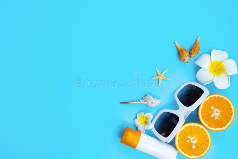 H?rlig sommarferie, strandtillbeh?r, apelsin, skal och sunblock p? bl?a bakgrunder arkivbild