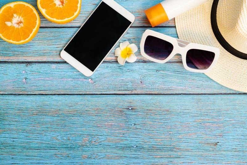 H?rlig sommarferie, strandtillbeh?r, apelsin, solglas?gon, hatt, sunblock och smartphone p? tr?bakgrunder arkivfoton