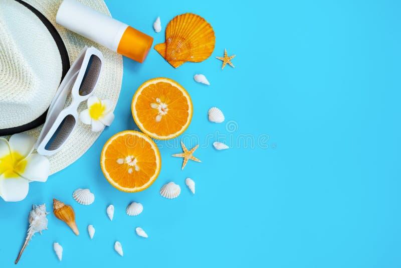 H?rlig sommarferie, strandtillbeh?r, solglas?gon, hatt, apelsin, sunblock och skal p? bl?a bakgrunder royaltyfri foto