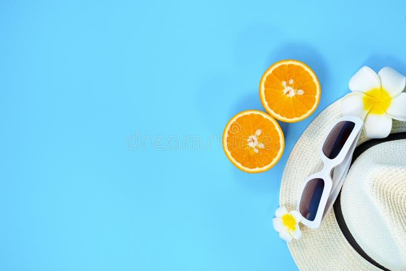 H?rlig sommarferie, strandtillbeh?r, solglas?gon, hatt och apelsin p? bl?a bakgrunder arkivfoto