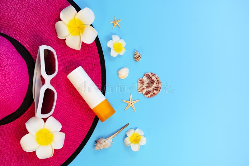 H?rlig sommarferie, strandtillbeh?r, solglas?gon, hatt, sunblock och skal p? bl?a bakgrunder royaltyfri bild
