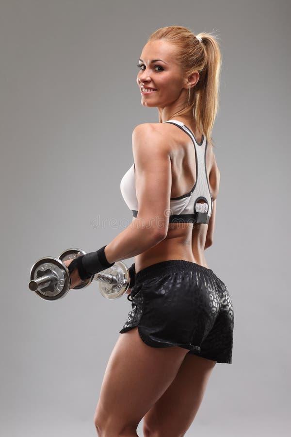 H?rlig sportig kvinna som utarbetar med hantlar arkivfoto