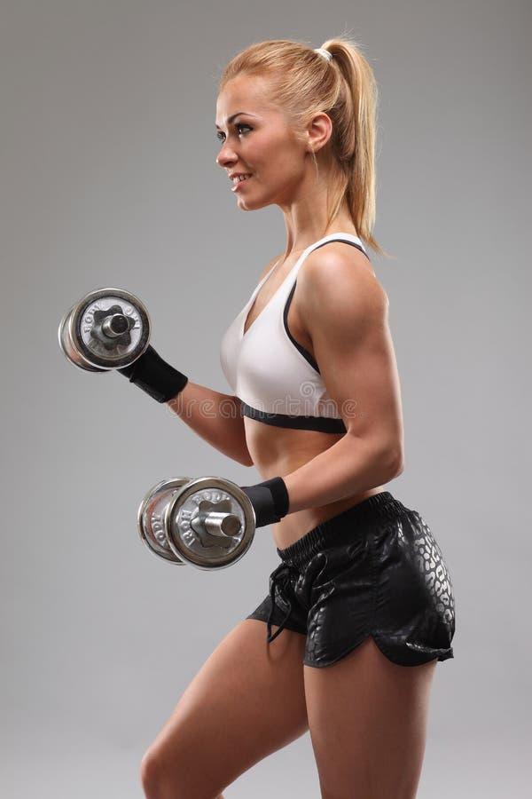 H?rlig sportig kvinna som utarbetar med hantlar royaltyfri fotografi
