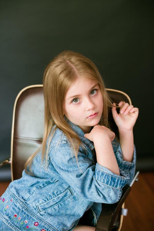 H?rlig trendig liten flicka med blont h?r i jeanskl?der p? en svart bakgrund royaltyfria foton
