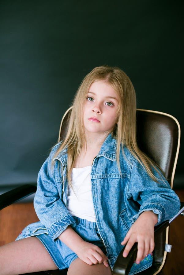 H?rlig trendig liten flicka med blont h?r i jeanskl?der p? en svart bakgrund arkivfoton