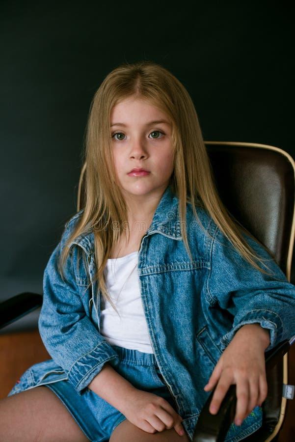 H?rlig trendig liten flicka med blont h?r i jeanskl?der p? en svart bakgrund royaltyfria bilder