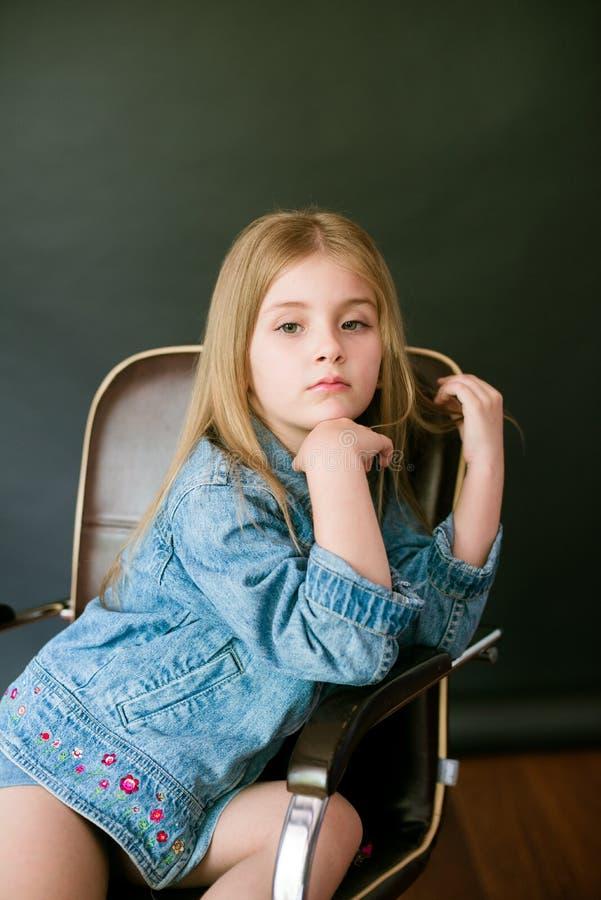 H?rlig trendig liten flicka med blont h?r i jeanskl?der p? en svart bakgrund royaltyfri fotografi