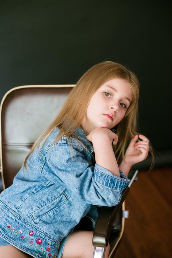 H?rlig trendig liten flicka med blont h?r i jeanskl?der p? en svart bakgrund royaltyfri foto