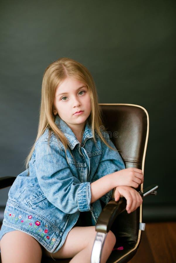 H?rlig trendig liten flicka med blont h?r i jeanskl?der p? en svart bakgrund arkivfoto