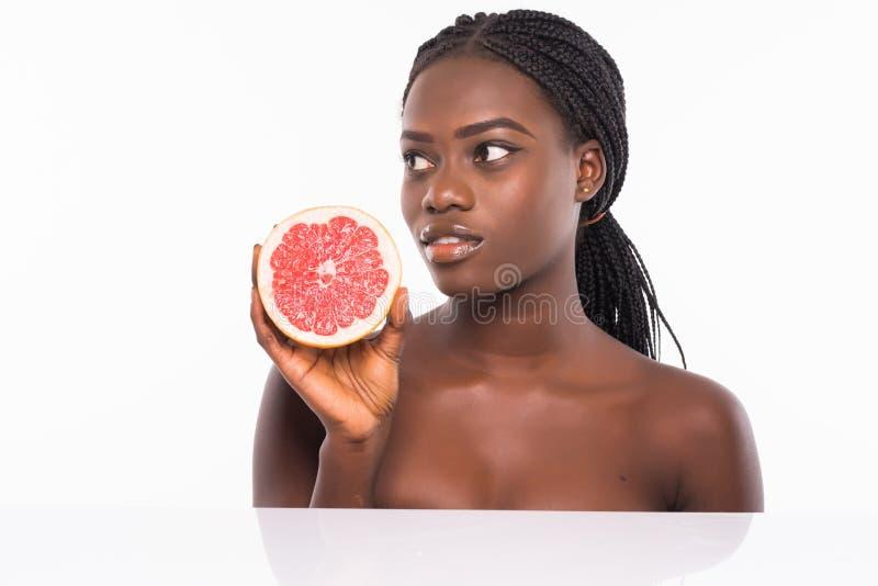 H?rlig ung afrikansk amerikankvinna som isoleras p? vit bakgrund Afro- flicka och att banta begrepp med orange frukt kopiera avst royaltyfri bild