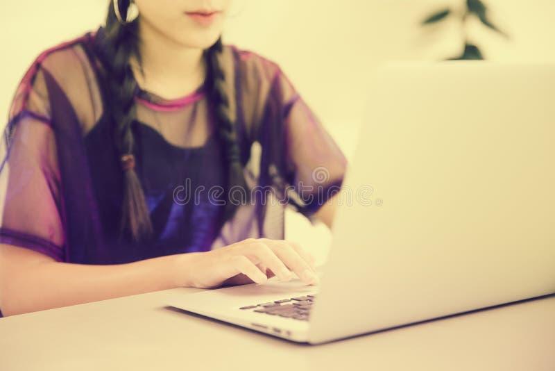 H?rlig ung asiatisk flicka som arbetar p? en coffee shop med en b?rbar dator arkivfoto