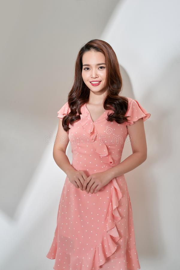 H?rlig ung asiatisk Lady som isoleras p? vit bakgrund hon har den trevliga kl?nningen royaltyfria foton