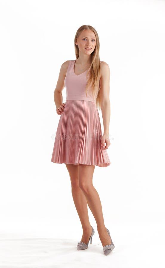 H?rlig ung blond kvinna i den rosa kl?nningen som isoleras p? vit bakgrund royaltyfri bild