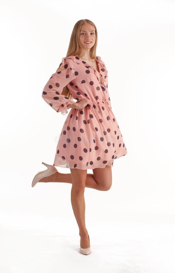 H?rlig ung blond kvinna i den rosa kl?nningen som isoleras p? vit bakgrund royaltyfria foton