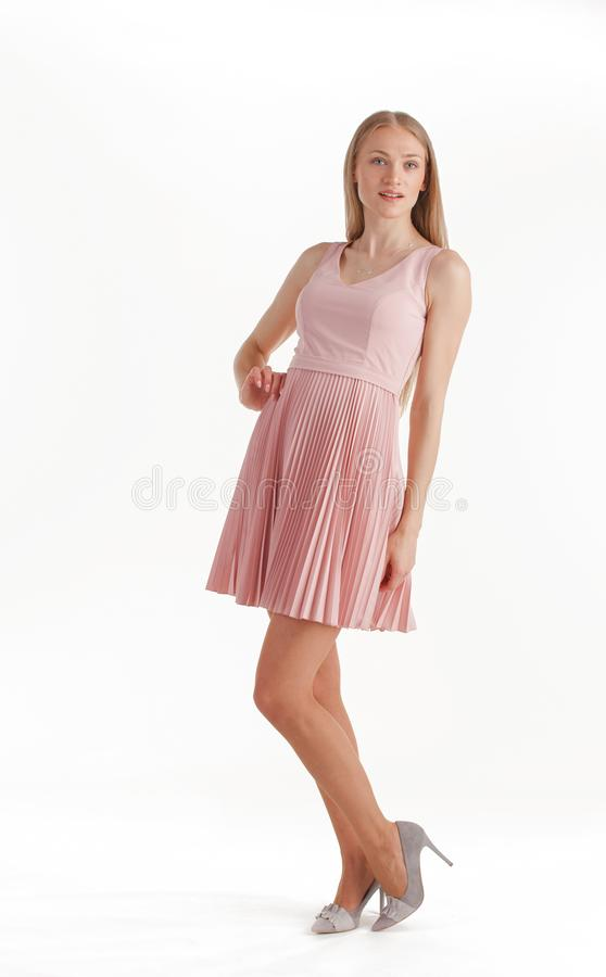 H?rlig ung blond kvinna i den rosa kl?nningen som isoleras p? vit bakgrund royaltyfria bilder
