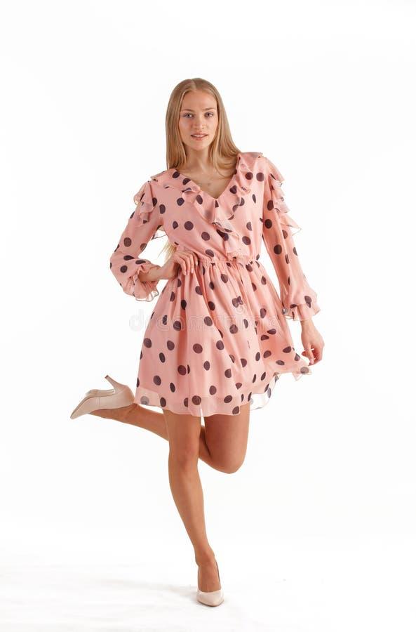 H?rlig ung blond kvinna i den rosa kl?nningen som isoleras p? vit bakgrund royaltyfri foto