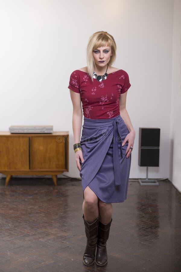 H?rlig ung blond kvinna som framme b?r den purpurf?rgade kjolen av den vita v?ggen arkivbilder