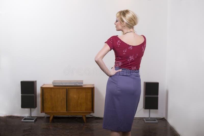 H?rlig ung blond kvinna som framme b?r den purpurf?rgade kjolen av den vita v?ggen arkivfoto
