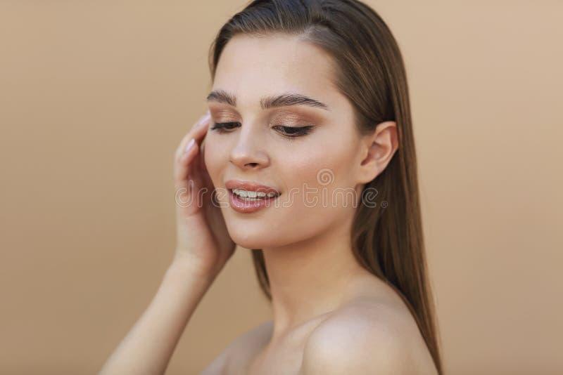 H?rlig ung brunettkvinna med ren ny hud som trycker p? eget h?r royaltyfria foton