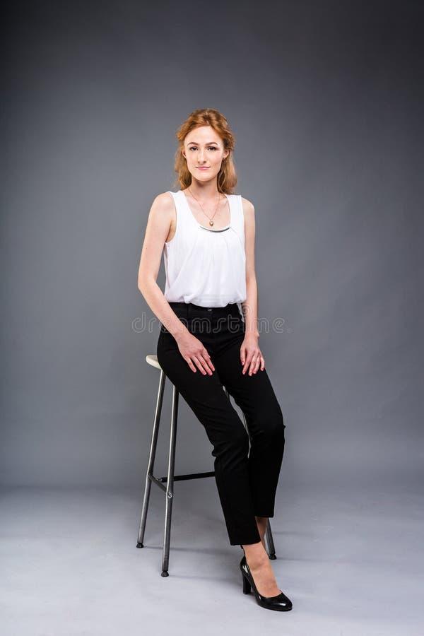 H?rlig ung caucasian kvinna med l?ngt r?tt h?r i h?ga h?l som in sitter p? en stol, en svart byxa och en vit skjorta arkivfoto