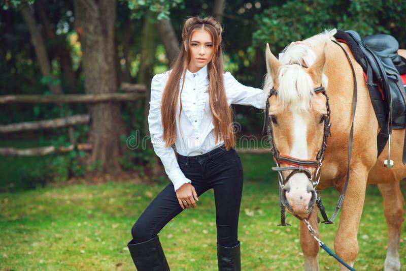 H?rlig ung flicka f?r st?ende i den vita skjortan och svarta fl?sanden med h?sten f?r l?ngt h?r f?r sk?nhet den n?sta i trendig e arkivfoto