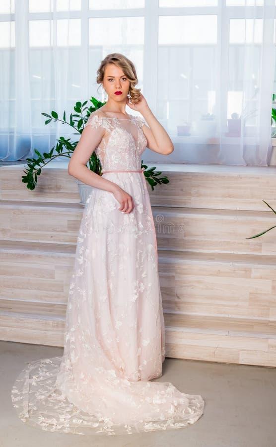 H?rlig ung flicka i en frodig elegant kl?nning i studion royaltyfria bilder