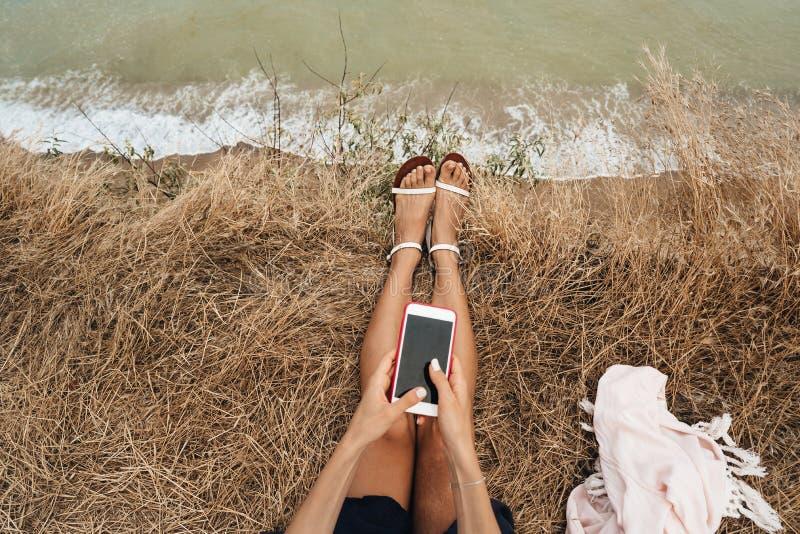 H?rlig ung flicka som sitter och rymmer en smartphone i hennes h?nder, b?sta sikt fotografering för bildbyråer