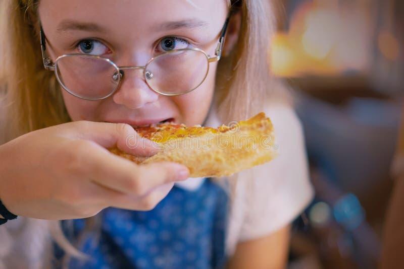 H?rlig ung flicka som ?ter en skiva av pizza royaltyfria bilder