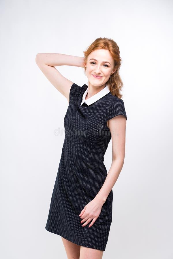 H?rlig ung flickastudent, sekreterare eller aff?rsdam med att charma leende och r?tt lockigt h?r i svart kl?nning i vit royaltyfria foton