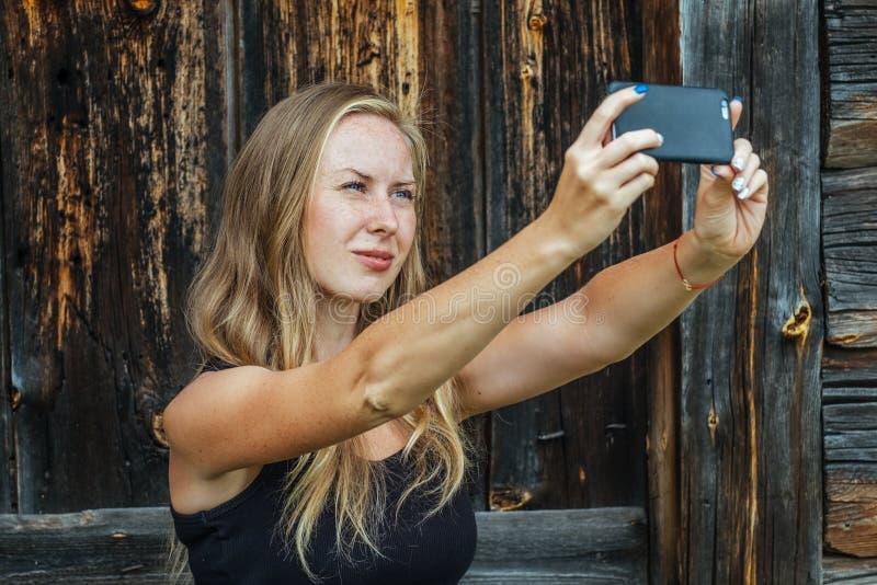 H?rlig ung fr?knig kvinna som anv?nder telefonen royaltyfria bilder